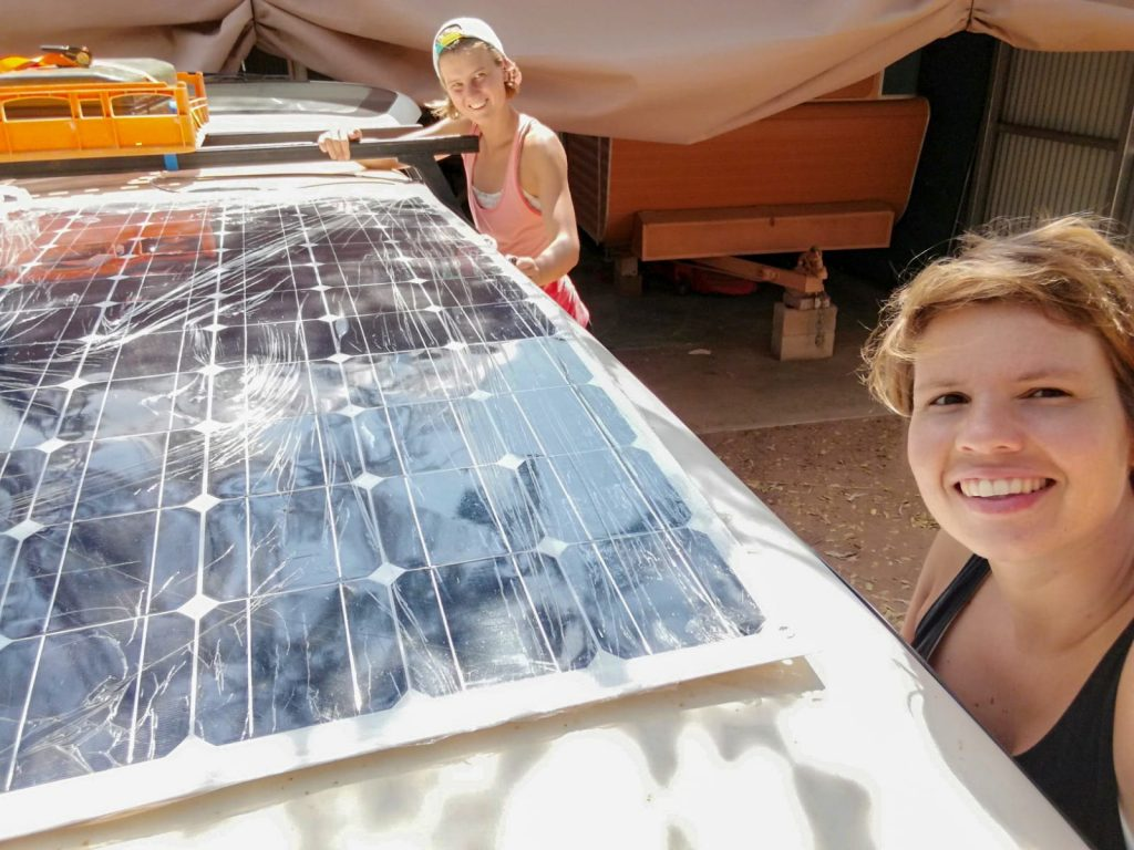 Kelly and Nanet standing next to the solar panel that is on top of their car to provide solar energy