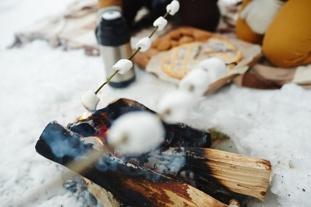 roasting marshmallows above fire while cold weather camping