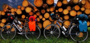 Best Bike Panniers attached to two tour bikes standing against a pile of wood