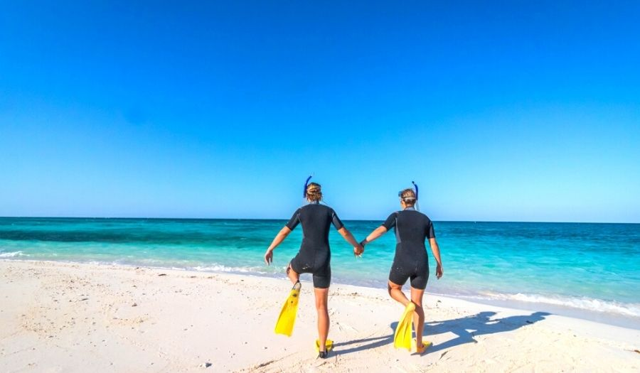 Kelly and Nanet dressed up in a wetsuit on the beach, ready to learn how to snorkel